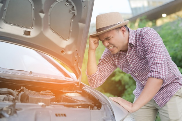 Młody zestresowany mężczyzna mający kłopoty ze swoim zepsutym samochodem stoi przed zepsutym samochodem wzywając pomocy.