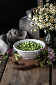 Młody zielony groszek w białym pucharze na drewnianym. groch kwitnie i stokrotka kwitnie na stole.