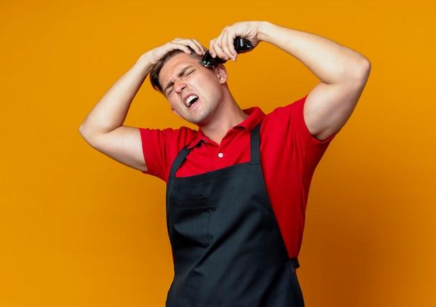 Młody zirytowany blond męski fryzjer w mundurze trzyma głowę przycinającą włosy maszynką do strzyżenia włosów odizolowaną na pomarańczowej przestrzeni z miejsca na kopię
