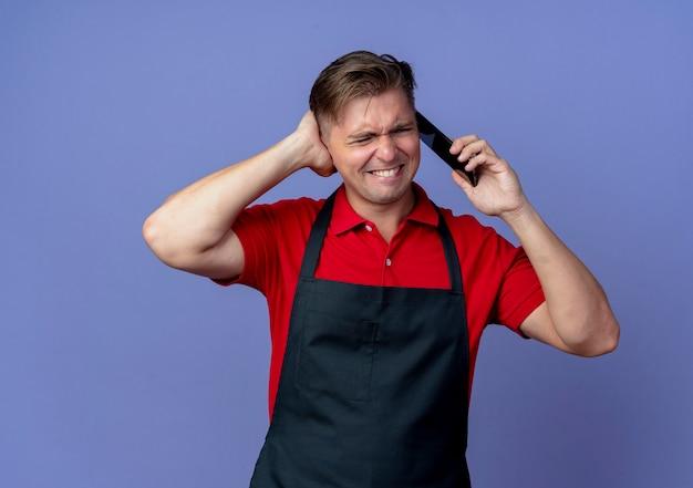 Młody zirytowany blond mężczyzna fryzjer w mundurze blokuje ucho ręką rozmawia przez telefon na białym tle na fioletowej przestrzeni z miejsca na kopię