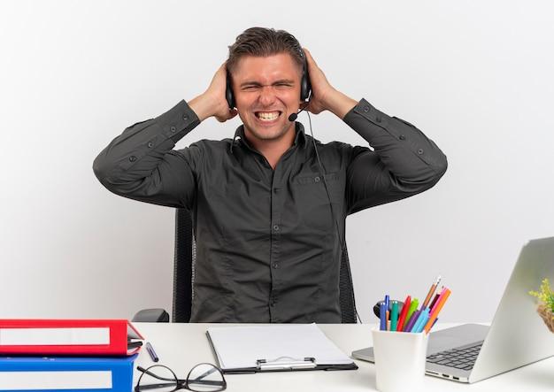 Młody zirytowany blond pracownik biurowy mężczyzna na słuchawkach siedzi przy biurku z narzędziami biurowymi za pomocą laptopa trzyma głowę z zamkniętymi oczami na białym tle z miejsca na kopię