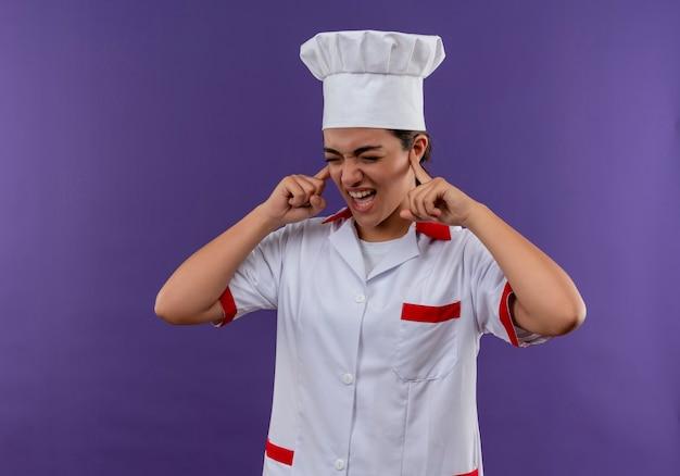 Młody zirytowany kucharz kaukaski dziewczyna w mundurze szefa kuchni zamyka uszy palcami na białym tle na fioletowym tle z miejsca na kopię