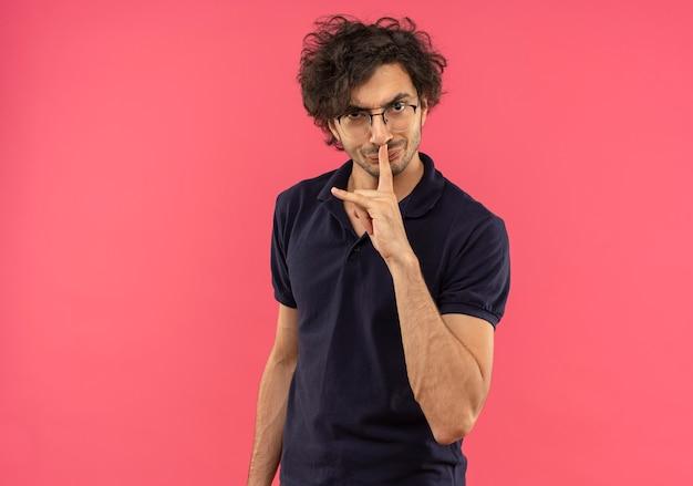 Młody zirytowany mężczyzna w czarnej koszuli z okularami optycznymi gestami ciszy na różowej ścianie
