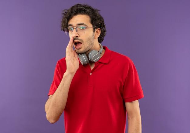 Młody zirytowany mężczyzna w czerwonej koszuli z okularami optycznymi i słuchawkami trzyma rękę na ustach, udając, że dzwoni do kogoś izolowanego na fioletowej ścianie