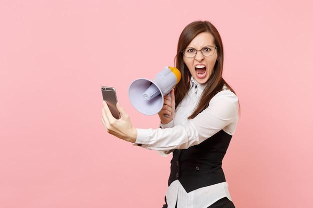 Młody zirytowany niezadowolony biznes kobieta w okularach krzyczy trzymając megafon i telefon komórkowy na białym tle na różowym tle. szefowa. osiągnięcie bogactwa kariery. skopiuj miejsce na reklamę.