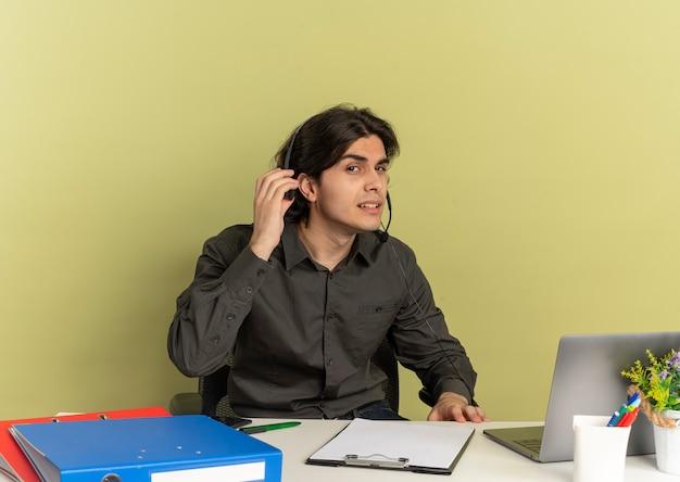 Młody zirytowany pracownik biurowy mężczyzna na słuchawkach siedzi przy biurku z narzędziami biurowymi za pomocą laptopa i trzyma słuchawki, próbując usłyszeć na białym tle na zielonym tle z przestrzenią do kopiowania