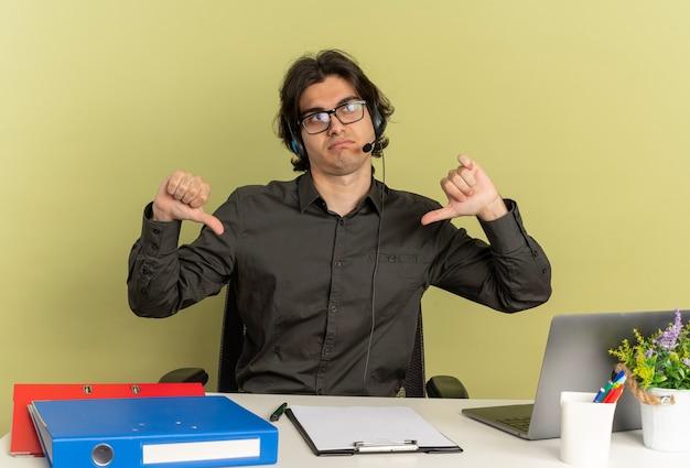 Młody zirytowany pracownik biurowy mężczyzna na słuchawkach w okularach optycznych siedzi przy biurku z narzędziami biurowymi za pomocą laptopa kciuk w dół na białym tle na zielonym tle z miejscem na kopię