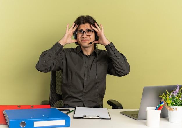 Młody zirytowany pracownik biurowy mężczyzna na słuchawkach w okularach siedzi przy biurku z narzędziami biurowymi za pomocą laptopa trzyma głowę i patrzy na bok na białym tle na zielonym tle z przestrzenią do kopiowania