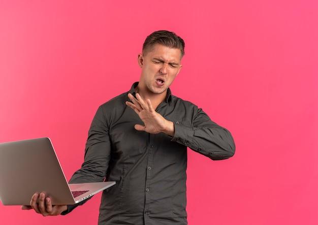 Młody zirytowany przystojny blondyn trzyma laptopa i trzyma rękę z zamkniętymi oczami na białym tle na różowym tle z miejsca na kopię