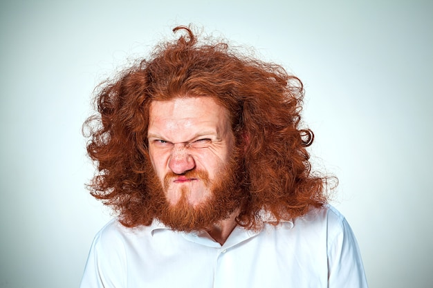 Młody zły człowiek z długimi rudymi włosami
