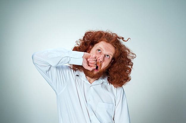 Młody, zły mężczyzna o długich rudych włosach bije się