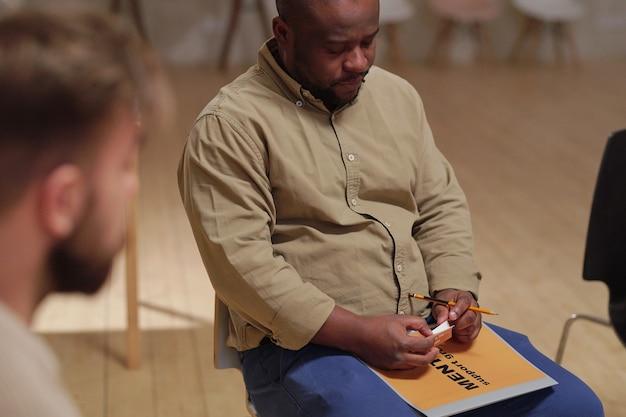 Młody zmartwiony mężczyzna pochodzenia afrykańskiego siedzący wśród pacjentów psychologa opisujący swój problem