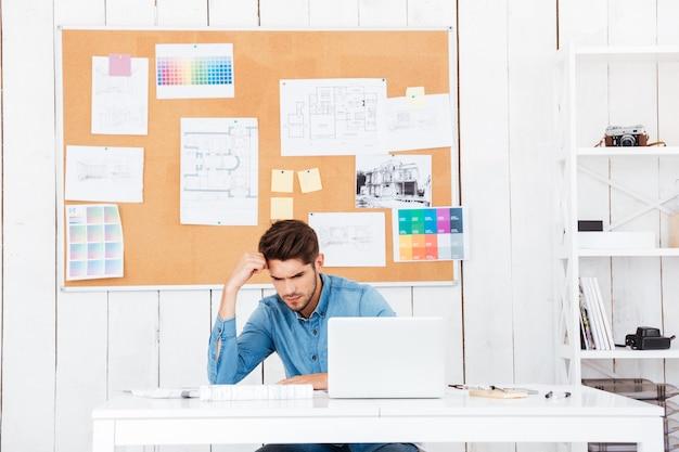 Młody zmęczony biznesmen siedzi z laptopem przy biurku w biurze