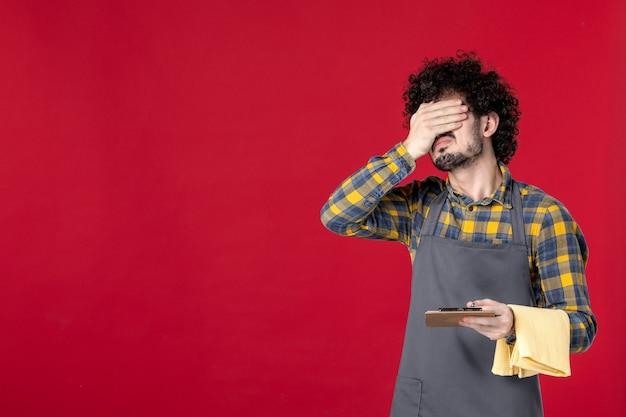 Młody zmęczony facet serwer z kręconymi włosami trzymający ręcznik przyjmujący zamówienie na odosobnionym czerwonym tle