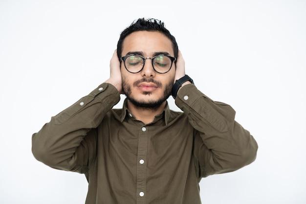 Młody zmęczony lub zirytowany mężczyzna w okularach, z zamkniętymi oczami i rękami na uszach, stojąc w izolacji