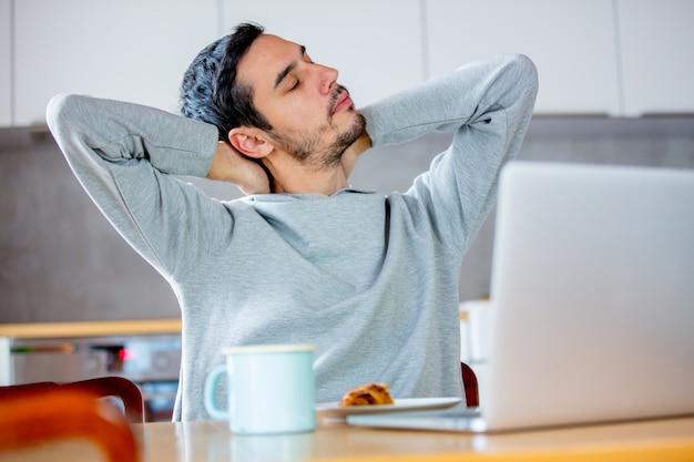 Młody zmęczony mężczyzna siedzi przy stole z komputerem claptop