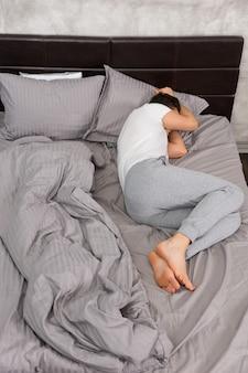 Młody zmęczony mężczyzna śpi bez koca w stylowym łóżku w szarych kolorach i obok stolika nocnego ze świecami w sypialni w stylu loft