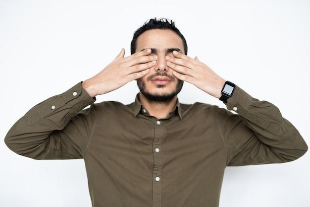 Młody zmęczony mężczyzna w koszuli zasłaniając oczy rękami w przerwie między pracą, jednocześnie relaksując się w izolacji