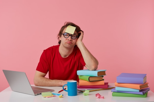 Młody zmęczony mężczyzna w okularach nosi czerwoną koszulkę, siedzi przy stole i pracuje z notatnikiem i książkami, z naklejką na czole, ze smutkiem patrzy w kamerę, odizolowany na różowym tle.