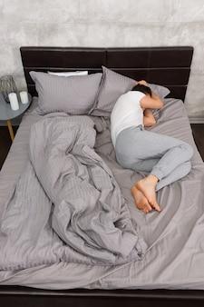 Młody zmęczony mężczyzna w piżamie śpiący bez koca w stylowym łóżku w szarych kolorach i przy nocnym stoliku ze świecami w sypialni w stylu loft