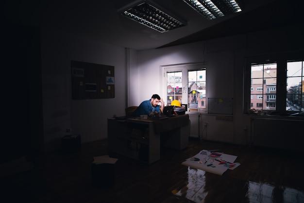 Młody zmęczony, rozczarowany biznesmen szuka rozwiązania problemu na laptopie, pozostając po normalnym czasie pracy w ciemnym biurze.