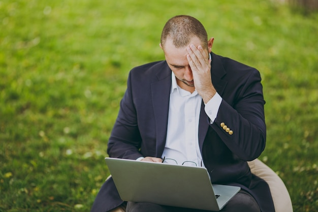 Młody zmęczony smutny biznesmen w białej koszuli, klasyczny garnitur, okulary. mężczyzna siedzi na miękkiej pufie, martwi się problemami, pracuje na komputerze typu laptop w parku miejskim na zielonym trawniku na zewnątrz. koncepcja mobilnego biura.