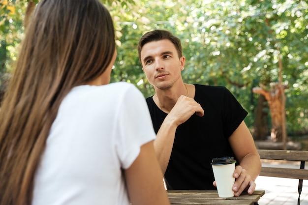 Młody znudzony człowiek siedzi i pije kawę