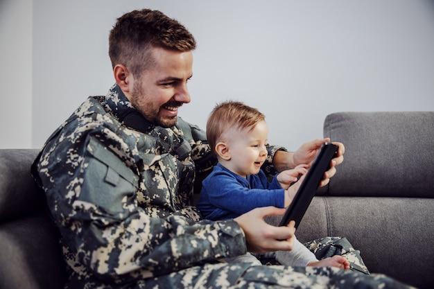 Młody żołnierz nadrabiający stracony czas. mężczyzna trzyma syna na kolanach, tablet w rękach i gra do ulubionej kreskówki swojego syna.
