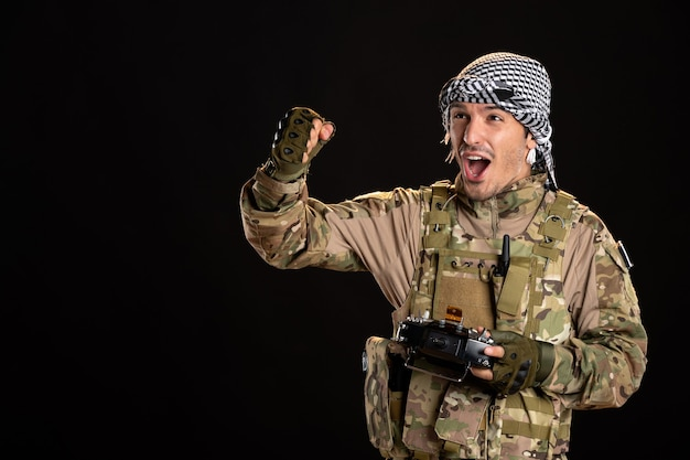 Młody żołnierz w kamuflażu używający pilota na ciemnej ścianie