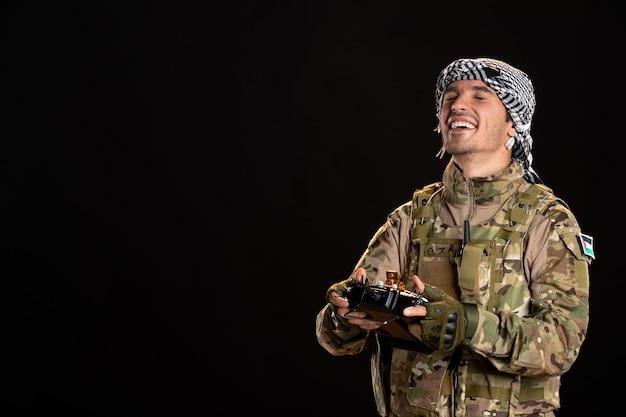 Młody żołnierz w kamuflażu używający pilota na czarnej ścianie