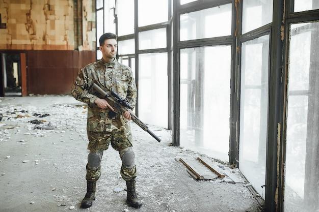 Młody żołnierz wojskowy patroluje budynek z dużym karabinem