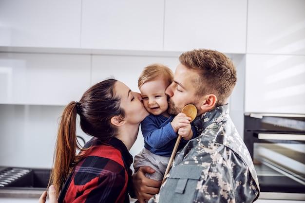 Młody żołnierz wrócił do domu i jest zadowolony ze swojej rodziny. mężczyzna i kobieta całują ukochanego jedynego syna.