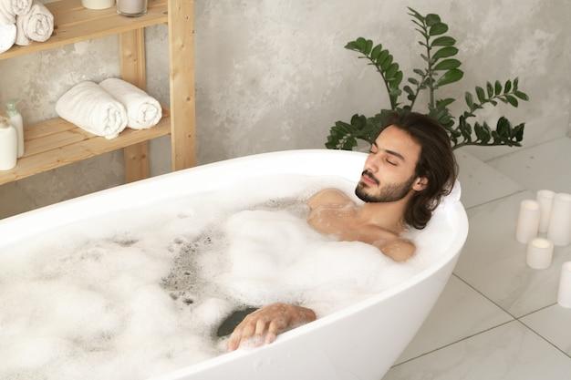 Młody zrelaksowany mężczyzna z zamkniętymi oczami leżący w białej wannie wypełnionej gorącą wodą i pianą z drewnianymi półkami w pobliżu