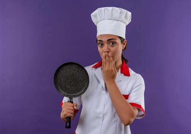 Młody zszokowany kaukaski kucharz dziewczyna w mundurze szefa kuchni trzyma patelnię i zamyka usta ręką odizolowaną na fioletowej ścianie z miejsca na kopię