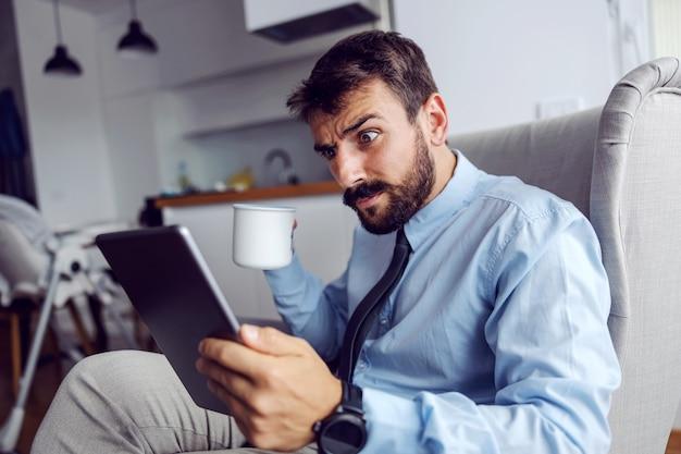 Młody zszokowany ojciec w garniturze siedzi w domu na krześle, pije kawę i czyta maile.