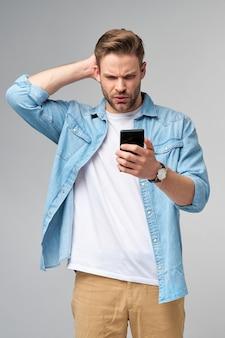 Młody zszokowany podkreślił zły i sfrustrowany mężczyzna za pomocą smartfona
