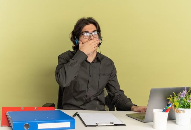 Młody zszokowany pracownik biurowy mężczyzna na słuchawkach w okularach optycznych siedzi przy biurku z narzędziami biurowymi za pomocą laptopa i patrząc na niego kładzie dłoń na ustach na białym tle na zielonym tle z przestrzenią do kopiowania