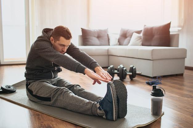 Młody zwykły człowiek uprawia sport w domu. początkujący lub amator podczas ćwiczeń siada na macie i rozciąga się po palce u stóp. pracowity facet ćwiczy w apartamencie samotnie.