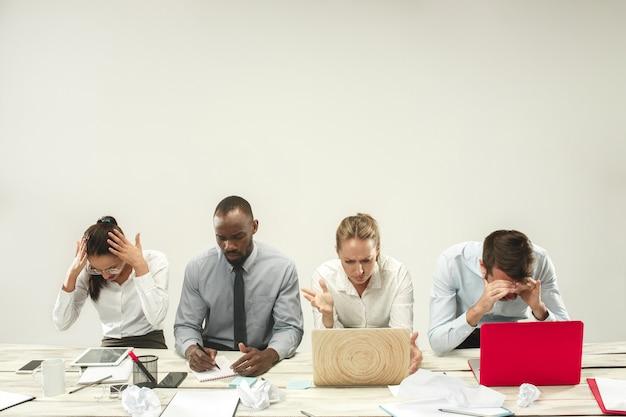 Młodych afrykańskich i kaukaskich mężczyzn i kobiet siedzących w biurze i pracy na laptopach. biznes, emocje, zespół, praca zespołowa, miejsce pracy, przywództwo, koncepcja spotkania. różne emocje kolegów