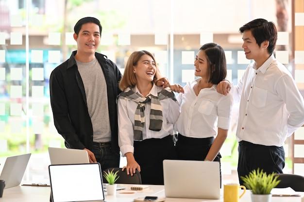Młodych biznesowych kolegów szczęśliwy moment w biurowym pokoju.