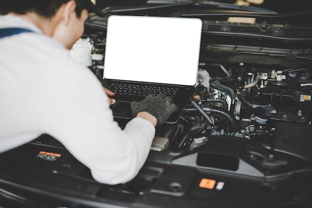 Młodych człowieków mechanik pracuje na komputerze łączącym samochodowy silnik