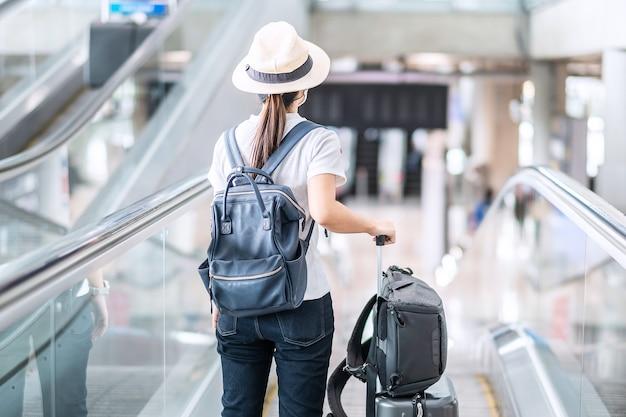 Młodych dorosłych kobiet noszących maskę w terminalu lotniska