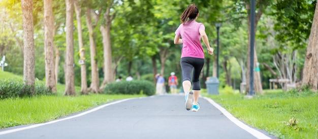 Młodych dorosłych kobiet w odzieży sportowej działa w parku na świeżym powietrzu