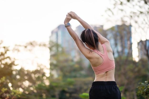 Młodych dorosłych kobiet w różowej odzieży sportowej rozciągających mięśnie w parku na świeżym powietrzu, kobieta sport rozgrzewka gotowa do biegania i joggingu rano. koncepcje odnowy biologicznej, fitness, ćwiczeń i równowagi między życiem zawodowym i prywatnym