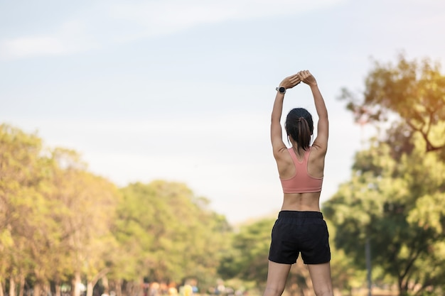 Młodych dorosłych kobiet w różowej odzieży sportowej rozciągających mięśnie w parku na świeżym powietrzu.