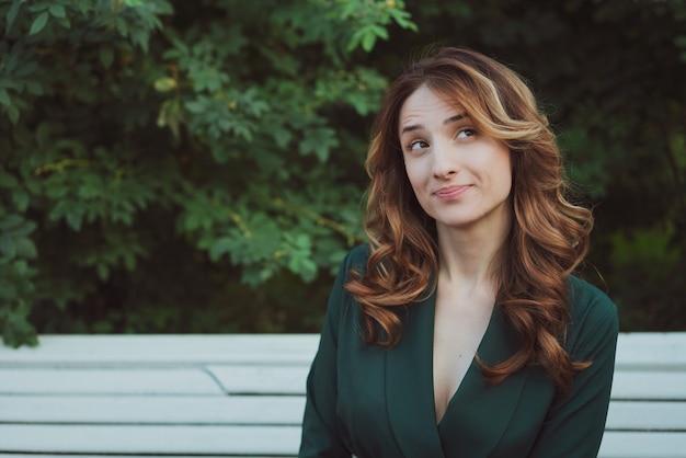 Młodych dorosłych piękna brunetka kobieta z długimi kręconymi włosami siedzi na ławce w zielonej sukience