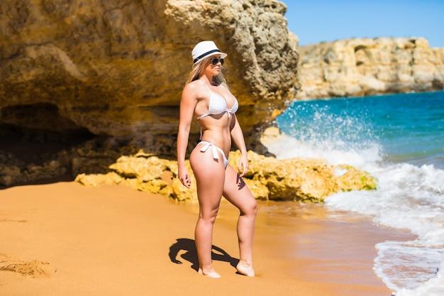 Młodych dorosłych szczupła atrakcyjna kobieta stwarzających z plaży