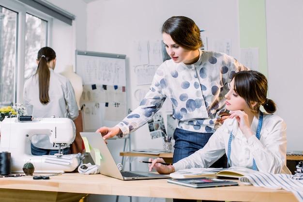 Młodych dziewczyn projektanci mody używa nowożytnego laptop i rysują nakreślenia dla nowej kolekci odziewają podczas gdy pracujący przy stołem w studiu. krawcowa kobieta biorąc pomiary manekin z taśmy środka