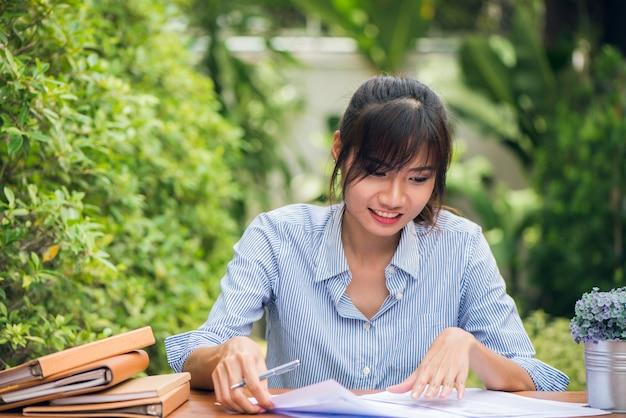 Młodych kobiet azjatyckich pisanie prac domowych na biurko w plenerze, kobieta pracująca z koncepcji szczęśliwy emocji. obrazy stylu efektów klasycznych.