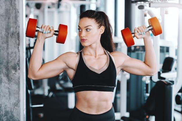 Młodych kobiet rasy kaukaskiej kulturysta podnoszenia hantle stojąc w siłowni.